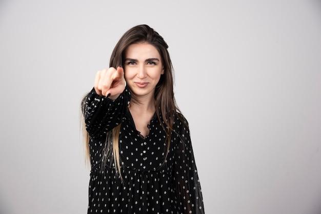 Femme souriante pointant vers la caméra sur un mur gris.