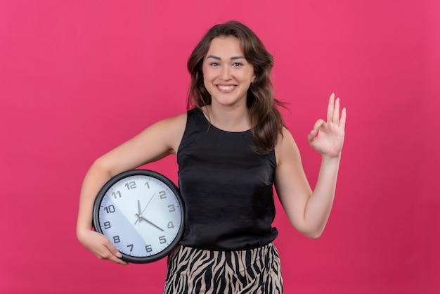 Femme souriante portant un maillot noir tenant une horloge murale et montre un geste okey sur un mur rose