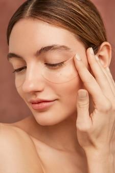 Femme souriante portant des patchs oculaires se bouchent