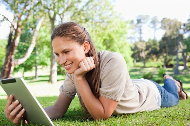 Femme souriante portant sur la pelouse avec son ordinateur tablette