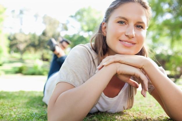 Femme souriante portant sur la pelouse