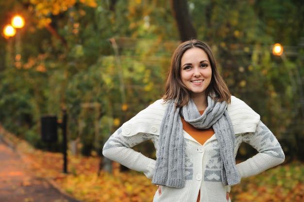 Femme souriante portant une veste tricotée dans le parc du soir d'automne.
