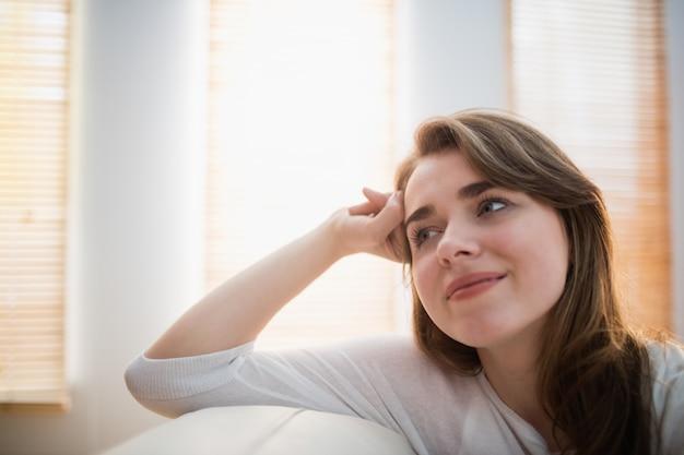 Femme souriante posant sur le canapé dans le salon