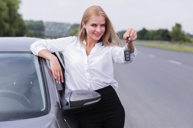 Femme souriante posant avec des clés de voiture