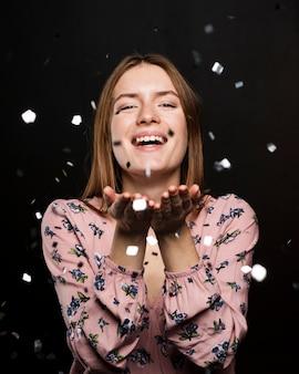 Femme souriante posant avec des confettis