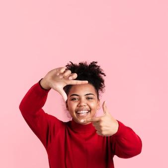 Femme souriante posant et faisant des doigts