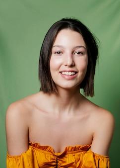 Femme souriante posant en haut jaune