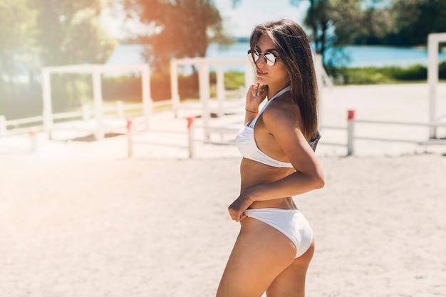 Femme souriante posant sur la plage