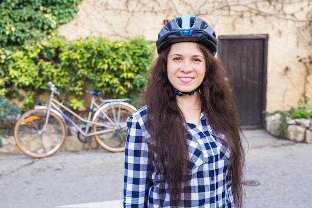 Femme souriante, à, position casque, sur, arrière-plan, bicyclette, et, allée