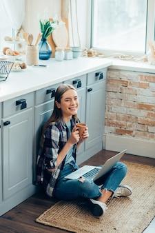 Femme souriante positive assise sur le sol de la cuisine avec une tasse et un appareil moderne