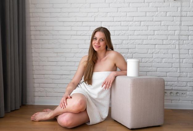 Une femme souriante et positive enveloppée dans une serviette de bain est assise près d'une chaise pouf avec un pot de pâte à sucre dessus. procédure d'épilation au spa, beauté, concept publicitaire