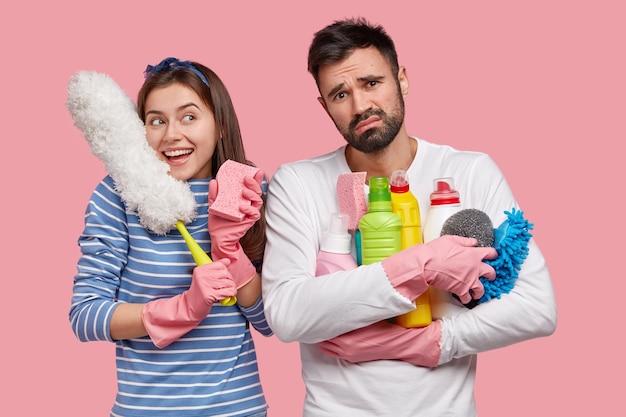 Femme souriante positive porte une brosse blanche, se réjouit des bons résultats après le nettoyage, un gars barbu bouleversé porte des détergents, semble fatigue, isolé sur espace rose