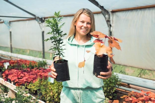 Femme souriante avec des pots de fleurs à l'intérieur de la serre description
