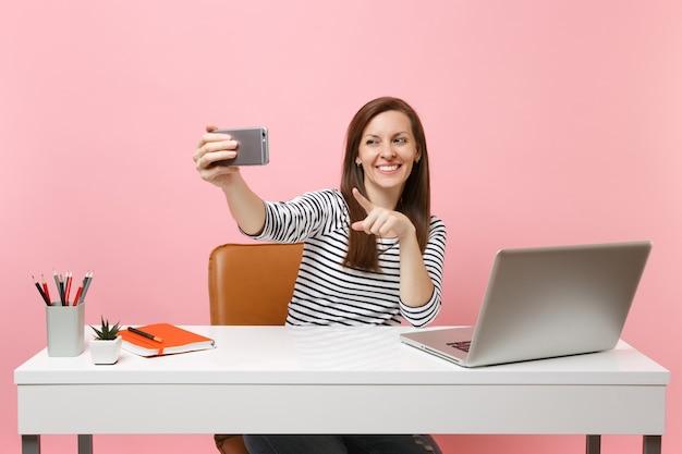 Femme souriante prenant une photo de selfie sur un téléphone portable tout en s'asseyant et travaillant au bureau blanc avec un ordinateur portable contemporain isolé sur fond rose pastel. concept de carrière d'entreprise de réalisation. espace de copie.