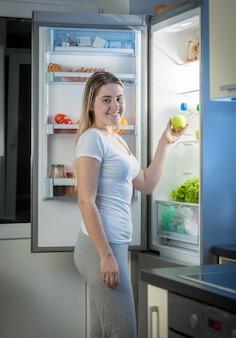 Femme souriante prenant une pomme verte du réfrigérateur la nuit