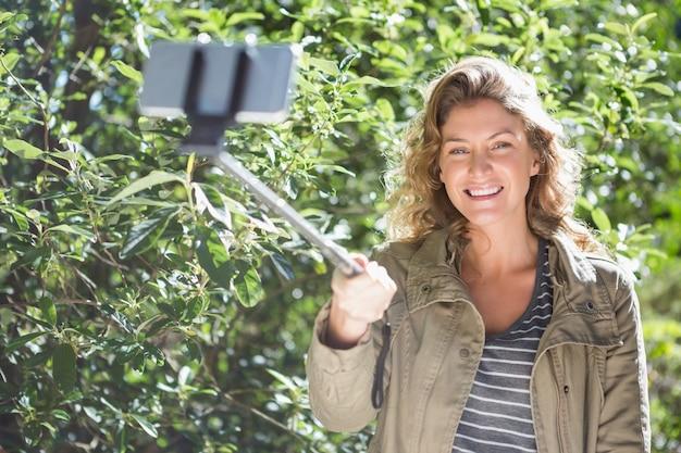 Femme souriante prenant des selfies