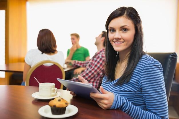 Femme souriante prenant son petit déjeuner tout en utilisant une tablette pc au café