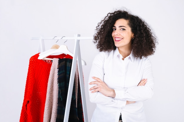 Femme souriante près de porte-vêtements