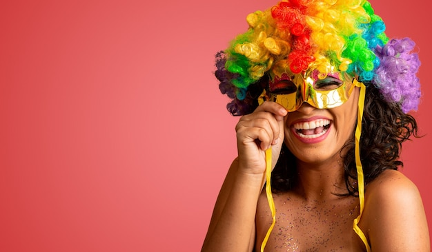 Femme souriante prête à profiter du carnaval avec une perruque et un masque colorés