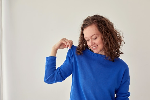 Femme souriante en pull bleu fond blanc