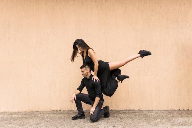 Femme souriante qui danse, sautant par-dessus l'épaule de l'homme