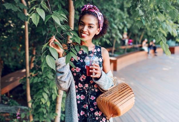 Femme souriante qui marche dans le parc ensoleillé et boire de la limonade