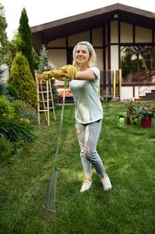Femme souriante avec râteau travaille dans le jardin