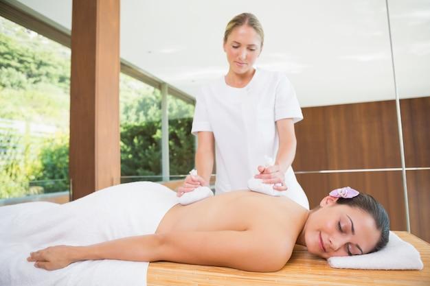 Femme souriante recevant un massage du dos avec des compresses aux herbes