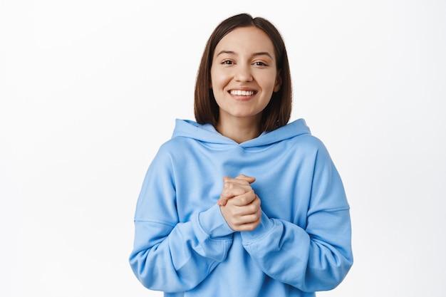Une femme souriante et reconnaissante tient les mains serrées, apprécie l'aide, merci, l'air ravie et reconnaissante, debout dans un sweat à capuche bleu contre un mur blanc
