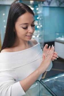 Femme souriante, regardant la bague chère qu'elle porte, shopping pour les bijoux