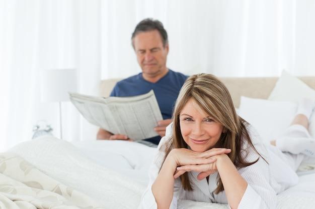 Femme souriante regardant la caméra pendant que son mari lit
