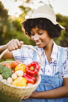 Femme souriante regardant un panier de légumes dans le jardin