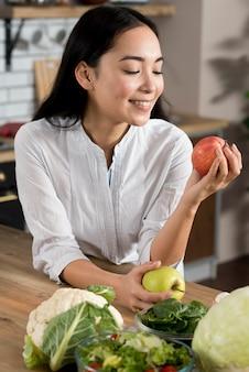 Femme souriante regardant une pomme rouge dans la cuisine à la maison