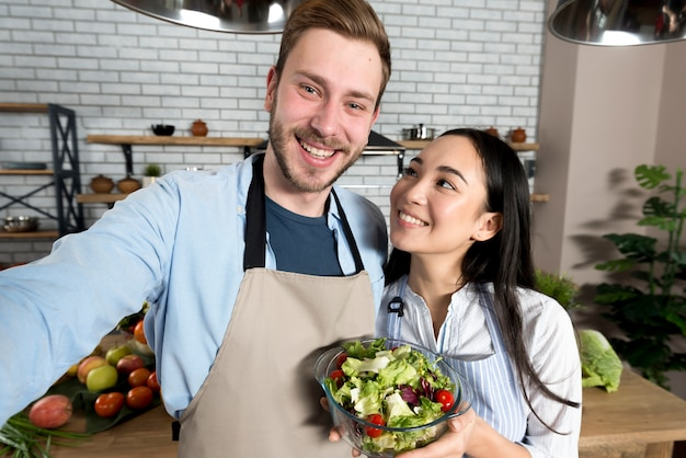 Femme souriante regardant son mari tenant une salade saine