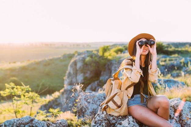 Femme souriante regardant à travers les jumelles
