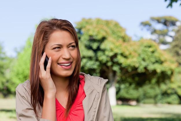 Femme souriante en regardant vers sa gauche dans une prairie ouverte