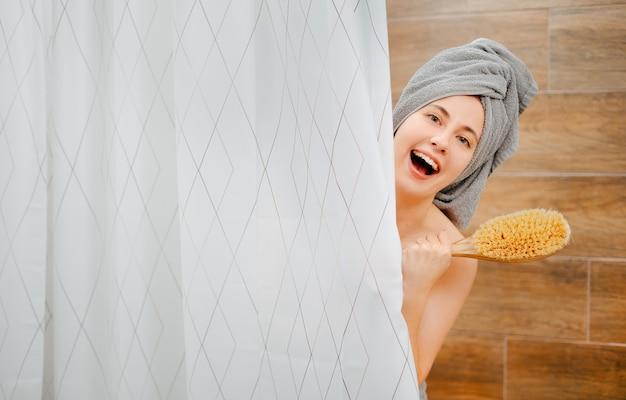 Une femme souriante regarde hors de la douche avec une brosse en bois pour le concept de massage corporel anticellulite