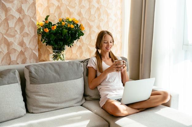 Femme souriante relaxante avec une tasse de thé en regardant un film comique sur ordinateur portable