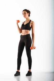 Femme souriante de remise en forme, faire de l'exercice avec des haltères