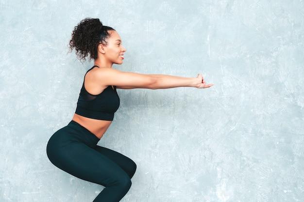 Femme souriante de remise en forme en vêtements de sport avec une coiffure afro curls