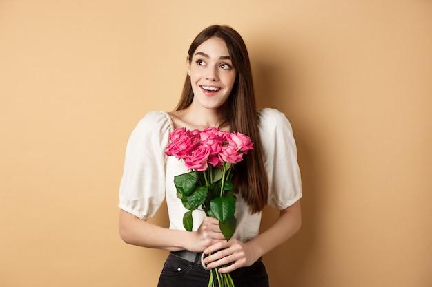 Une femme souriante rêveuse reçoit un bouquet de roses roses et regarde de côté avec amour