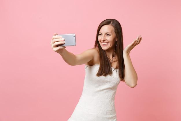 Femme souriante en robe blanche écartant les mains, prenant une photo de selfie sur un téléphone portable ou passant un appel vidéo