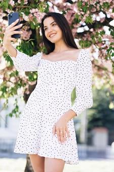 Femme souriante en robe blanche d'été prenant des photos d'autoportrait selfie sur smartphone