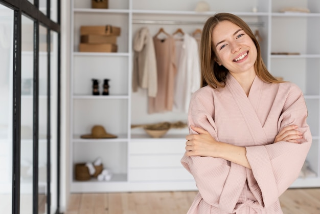 Femme souriante en robe rose, regardant la caméra