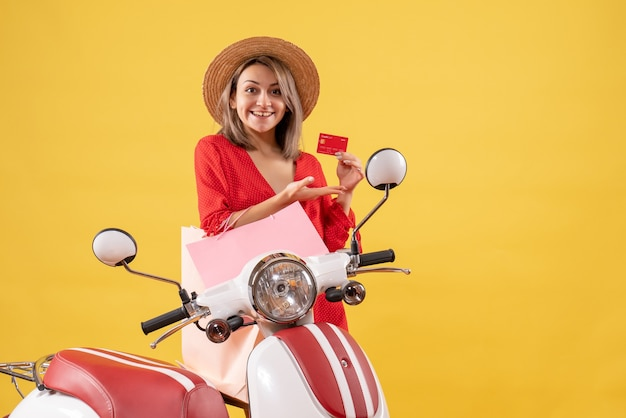 Femme souriante en robe rouge sur un cyclomoteur tenant des sacs à provisions et une carte