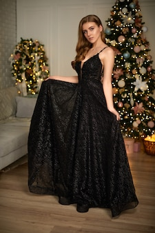 Femme souriante en robe de soirée sur l'arbre de noël