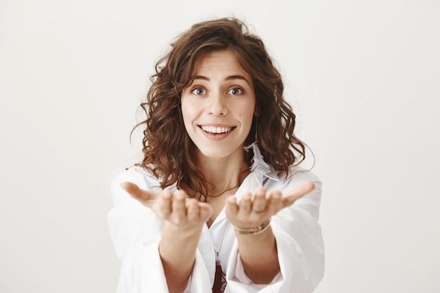 Femme souriante romantique vous louant, tendez les mains comme pour donner quelque chose