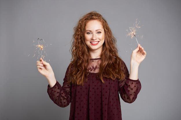 Femme souriante s'amusant avec des cierges magiques