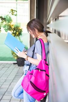 Femme souriante avec sac à dos, livre de lecture