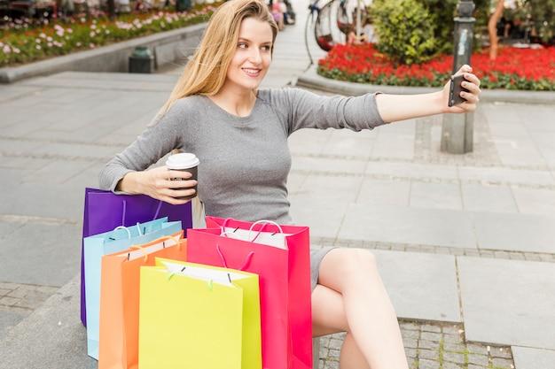 Femme souriante avec des sacs à provisions multicolores prenant selfie